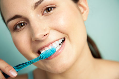 A woman brushing her teeth to protect her oral health!