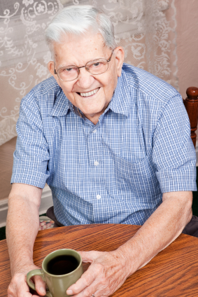 Elderly man with dentures smiling while drinking coffee - Bradshaw Family Dental